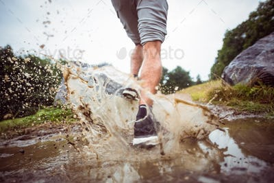 Man jogging through muddy puddles in the countryside