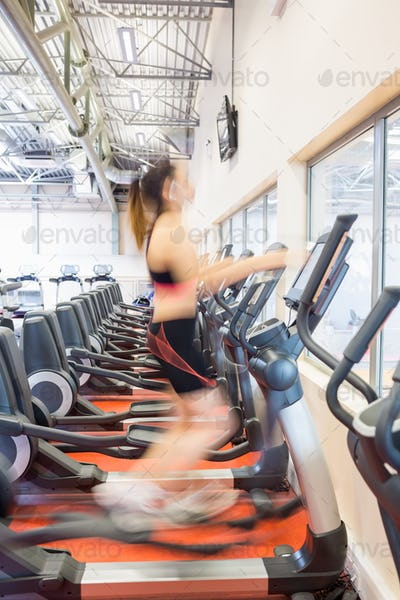 Focused woman on the cross trainer at the gym
