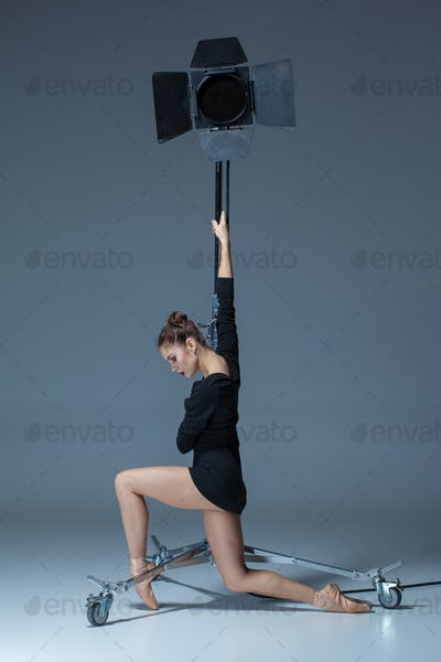 The beautiful ballerina posing on dack blue background
