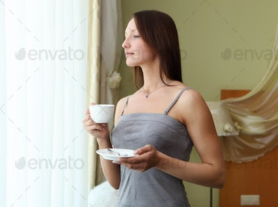 young woman drinking tea near the window