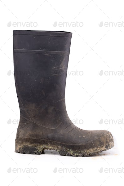 Muddy rubber boot side view isolated on white background