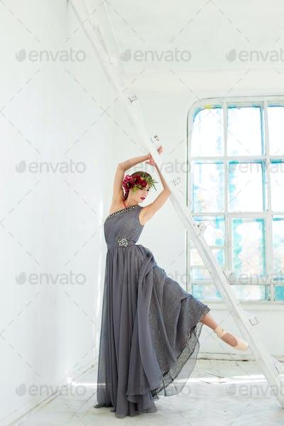 The beautiful ballerina posing in long gray dress