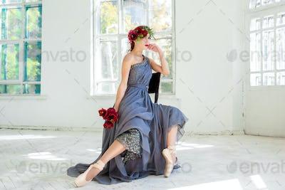 The beautiful ballerina sirtting in long gray dress