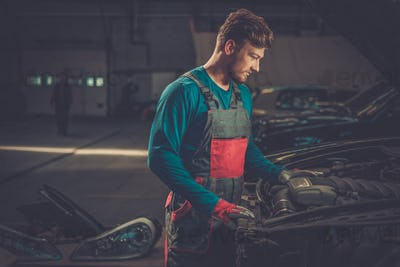 Mechanic checking under hood in a workshop