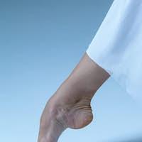 Close-up ballerina's leg on the blue floor