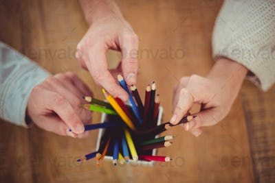 Creative team choosing different coloured pencils in casual office