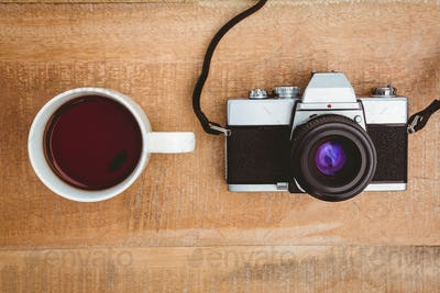 View of an old camera and a coffee on wood desk