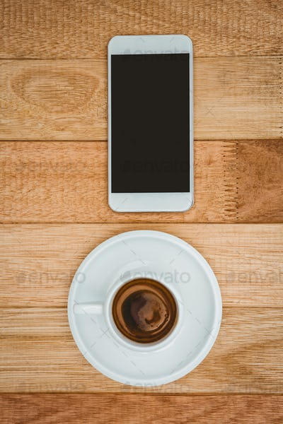 Above view of a coffee and a smartphone on wood desk