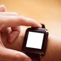 Asian woman using smart watch with copy space at home in the living room