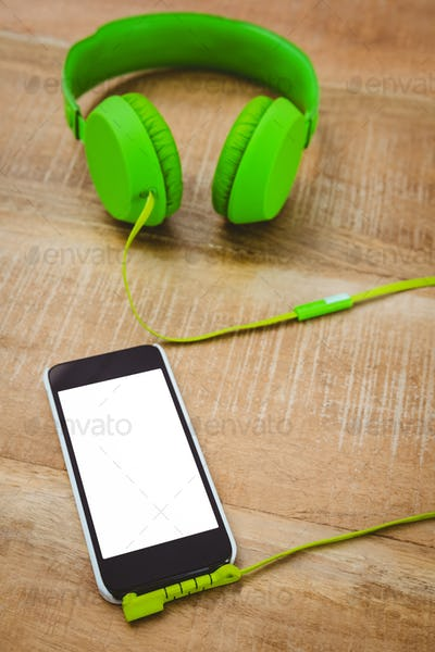 Green headphone with a back smartphone on wood desk
