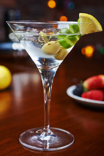 glass of cold martinis with olives with creative decoration lime and lemon. soft focus.