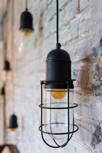 some beautiful vintage luxury interior lamps light on the background of a brick wall.