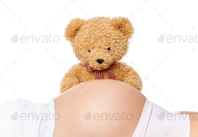 Teddy bear looking at belly of a pregnant woman
