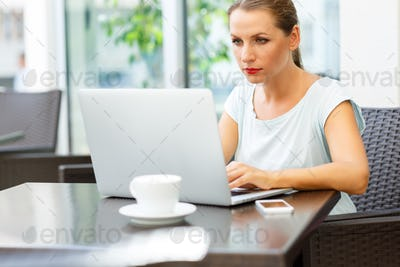 Young business woman sitting in a cafe with a laptop and coffee