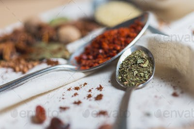 mix of different spices and herbs on a table with decor