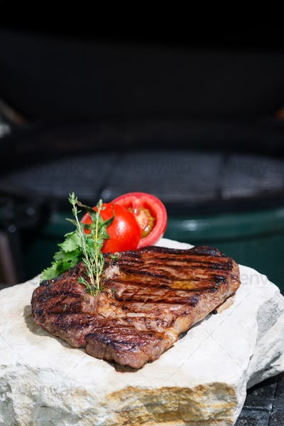 ready piece of grilled steak with a grill in the background focus on different parts of the meat