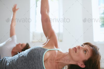 Fit woman doing half Moon pose in yoga class