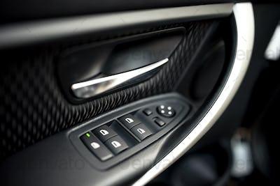 car interior details of door handle with windows controls