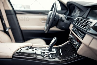 Modern beige and black interior of modern car, close-up of automatic transmission