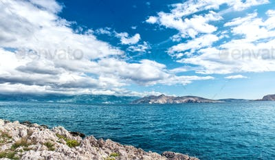 Panoramic view of island coastline landscape, calm water, clear sky on a sunny vacation day