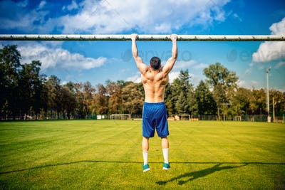 atheltic man doing chinups and core training in park. football player training on grass court
