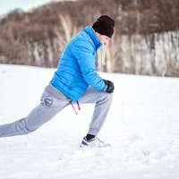 Fitness concept - male athlete stretching on snow