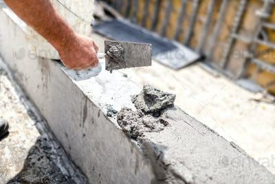 Construction worker leveling concrete with putty knife at building site.