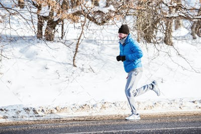 Fitness trainer working out on snow on a cold winter day in the