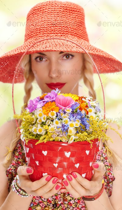 Woman on summer meadow with basket of wildflowers