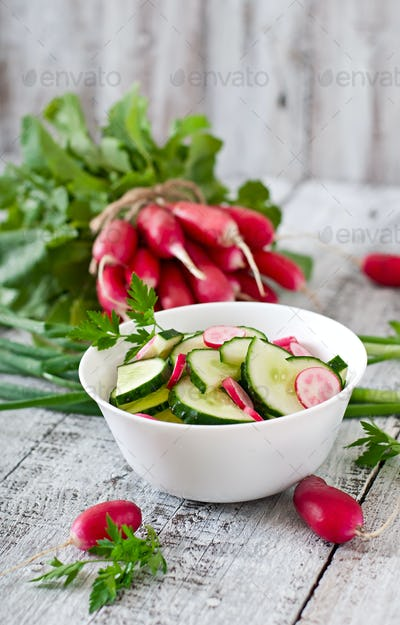 Fresh salad of cucumbers and radishes in a white bowl on the old wooden background