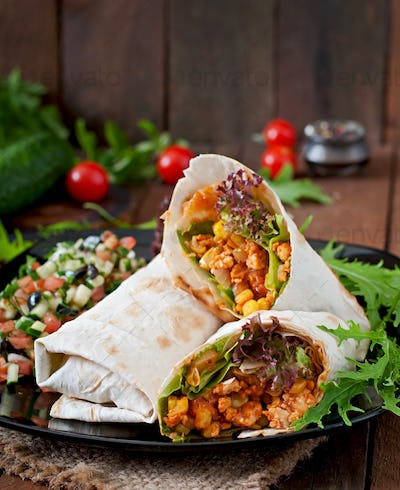 Burritos wraps with minced beef and vegetables on a wooden background.
