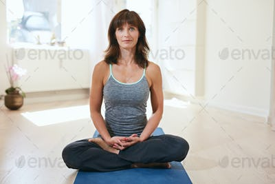 Woman meditating in yoga pose at gym