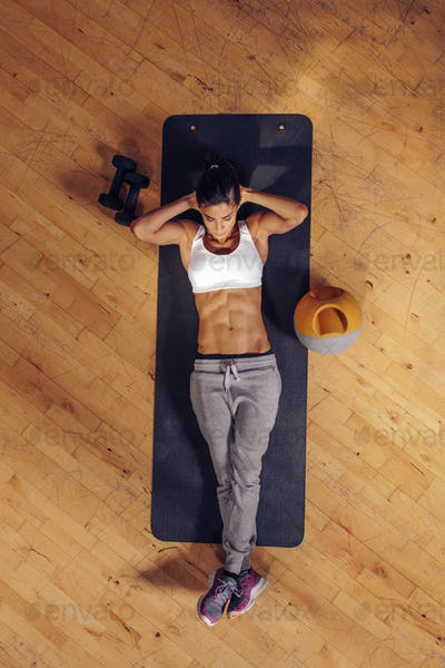 Fit young woman doing stomach exercises