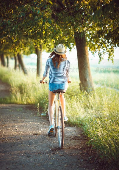 Girl in a hat riding a bicycle in a park - view from the back