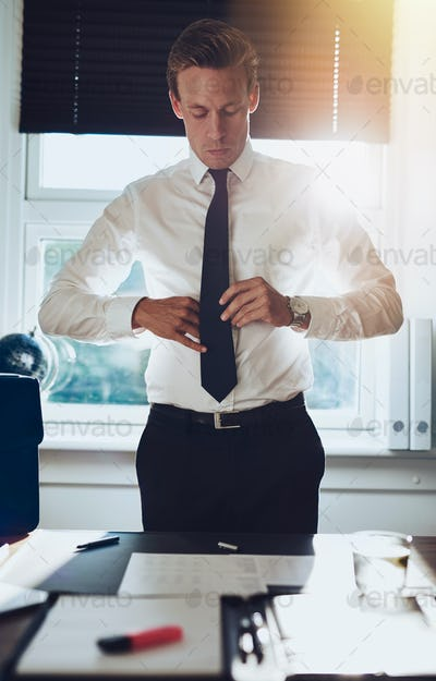 CEO executive business type white male tying his tie