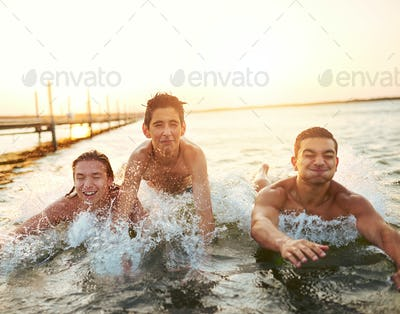 Three young boys splashing through the water