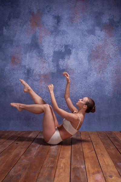 Young beautiful dancer in beige swimwear dancing on lilac background