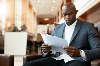 Young african businessman at hotel lobby reading documents