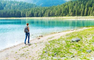 Traveler is walking on the lake coast