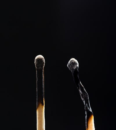 Two burned out wooden matches on black