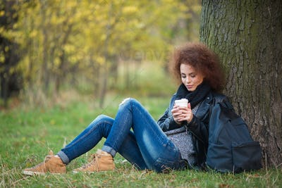 Attractive woman sitting under tree with cup of coffee
