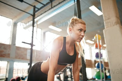 Fitness woman doing push ups in gym
