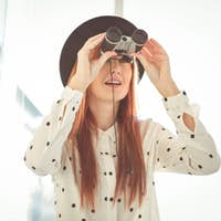 Smiling hipster woman using binoculars in a bright room