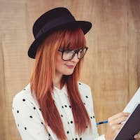 Attractive hipster woman writing on notepad against wooden background