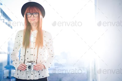 Portrait of smiling hipster woman in a bright room