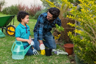 Smiling father and son gardening together