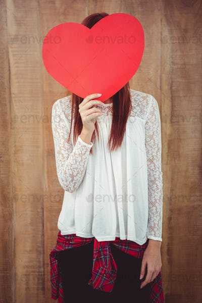 Smiling hipster woman behind a big red heart against wooden background