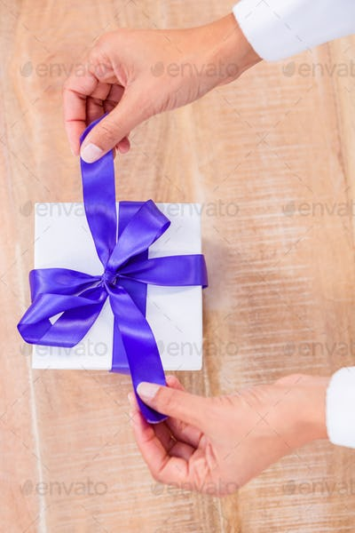 Woman presenting gift with purple ribbon on desk