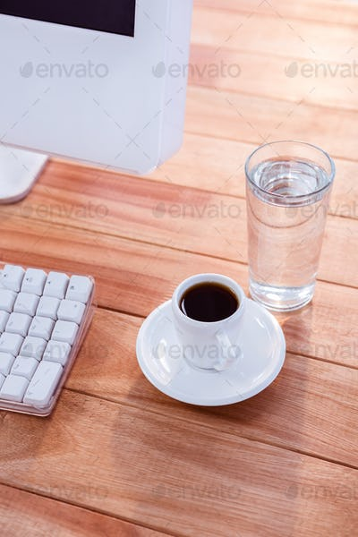 Close up view of a cup of coffee on wooden desk