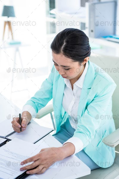Smiling businesswoman writing into a notepad at the desk in work